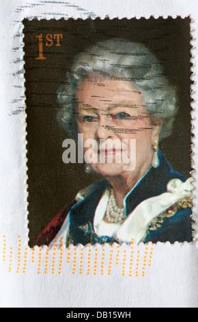 Sello de primera clase que muestra a la Reina Elizabeth II pegada en sobre blanco