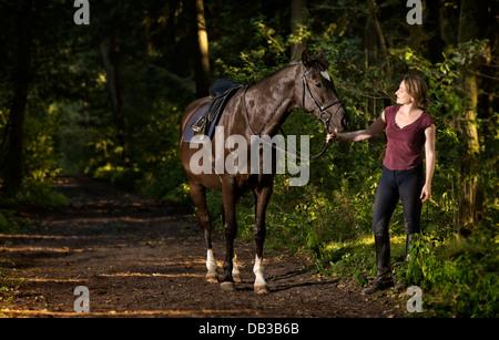 Mujer de 35 años, con su Trakehner en un camino forestal en la noche