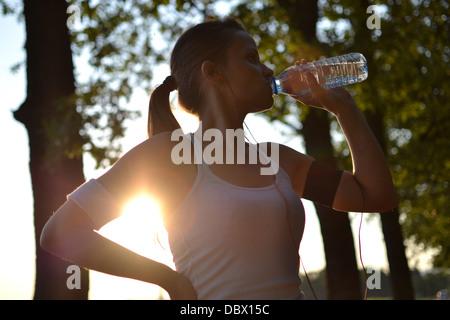 Mujer joven del agua potable durante su entrenamiento
