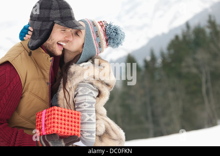 Pareja feliz con su regalo de Navidad besándose en campo nevado Foto de stock
