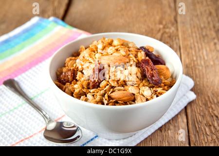 Müsli (granola) cerrar con cuchara, frutos secos, nueces y cereales en el tazón blanco sobre fondo de madera (tabla). La comida saludable.