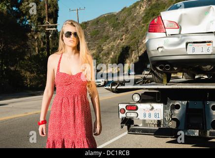 Mujer joven mirando a la cámara como Tow Truck quita auto dañado