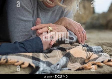 Pareja tumbado en la playa cogidos de la mano, más cerca