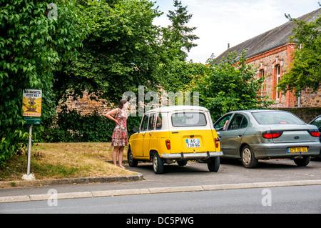 Mujer de pie junto a su viejo Renault 4 amarillo, estacionado en Clécy (en el departamento de Calvados Normandía, noroeste de Francia).