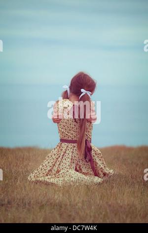 Una chica en VINTAGE DRESS, sentado en una pradera, abrazarse a sí misma