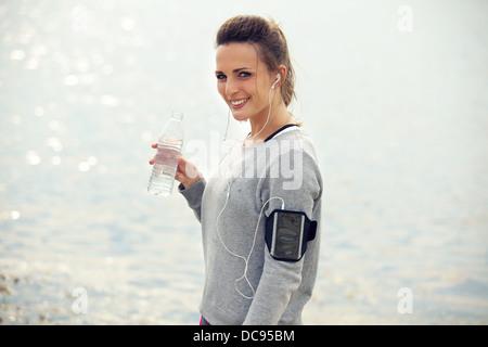 Feliz corredoras sonriendo mientras mantiene un agua embotellada
