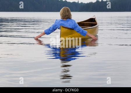 Mujer en canoa mano final en agua, Algonquin Park, Ontario, Canadá