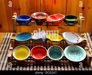 Coloridos recipientes vidriados aparece en el soporte de madera