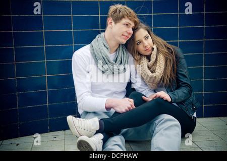 Cool adolescente joven pareja sentada en el suelo Foto de stock