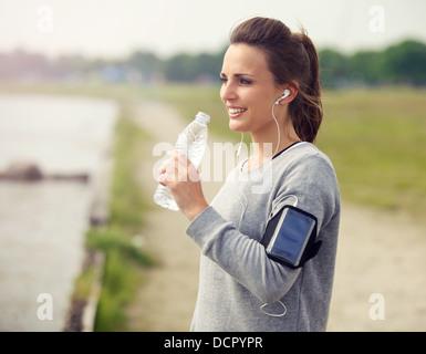 Corredoras sonriendo mientras bebe agua embotellada