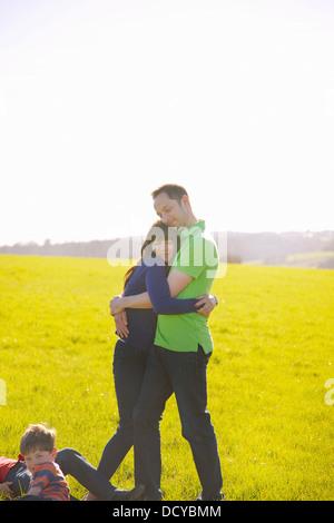 Par abrazar en el campo y los niños tumbados sobre el césped