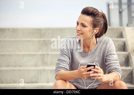 Feliz atleta atractivo sentarse y escuchar música mp3 mientras descansa