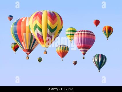 Un grupo de coloridos globos aerostáticos flotando en el cielo Foto de stock