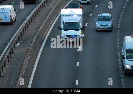 Un vehículo del servicio de ambulancias escocés corre rápidamente por la autopista M8 con sirenas y luces azules a un accidente.
