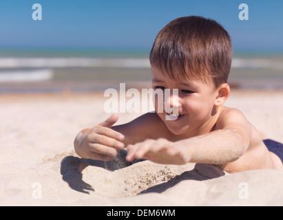 Feliz sonriendo cute little boy jugar con arena en la playa. Niño de tres años. El lago Huron, en Ontario, Canadá.