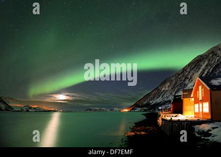 Rojo cabañas de pesca en el fiordo en invierno con las luces del norte, Troms Sommeroya, Tromsø, Noruega, el norte de Noruega. Foto de stock