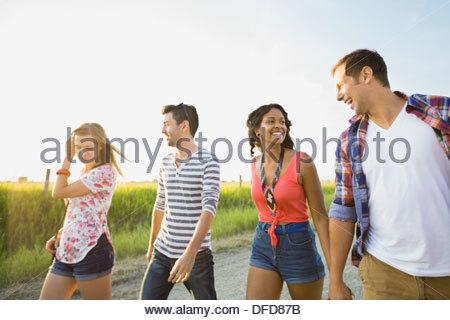 Jóvenes amigos caminando en el país por carretera Foto de stock