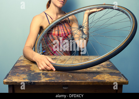 Mujer joven está sentado en una mesa con un neumático de bicicleta