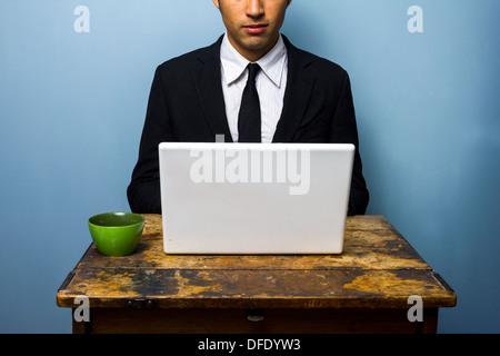 Joven Empresario de beber café y trabajar en su portátil.