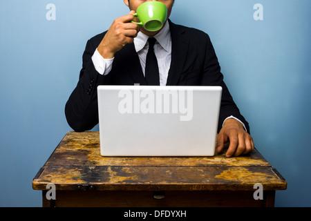Joven empresario está bebiendo café y trabajando con su ordenador portátil en un viejo escritorio
