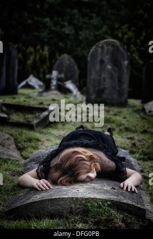 Una mujer está acostada en una tumba Foto de stock