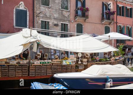 En Venecia, un mercado flotante operan desde una barcaza protegidas del sol por hojas (Italia). Marché flottant à Venise (Italie).