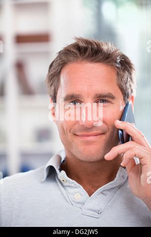 Macho maduro feliz hablando por teléfono móvil en interiores