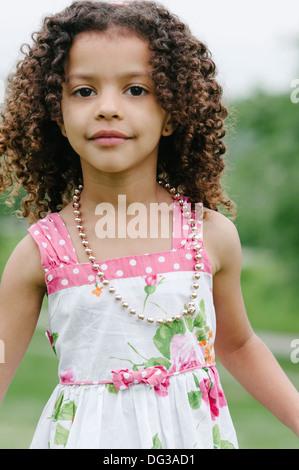 Niña con cabello castaño rizado vistiendo ropa de verano y Collar, Retrato