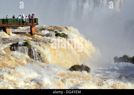 Brasil, el Parque Nacional Iguazú: Turistas Apreciar las Cataratas del Iguazú con registro de los niveles de agua desde una plataforma panorámica Foto de stock