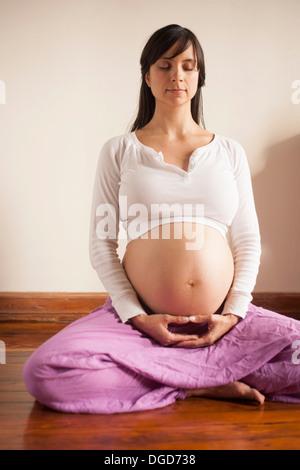 Mujer embarazada meditando sentado en el suelo