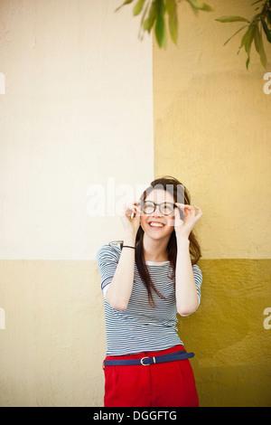 Retrato de mujer joven en frente de la pared dividida en color