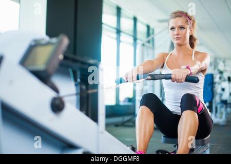 Mujer joven con máquina de remo en el gimnasio