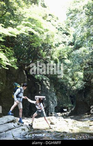 Un hombre ayuda a una mujer durante una caminata en el bosque