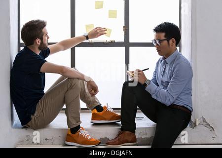Dos hombres jóvenes diseñadores compartir ideas sobre post-it notes