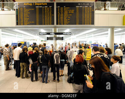 Los pasajeros esperando en línea en el check-in, junta de salida, el aeropuerto de Stuttgart, Baden-Wurtemberg