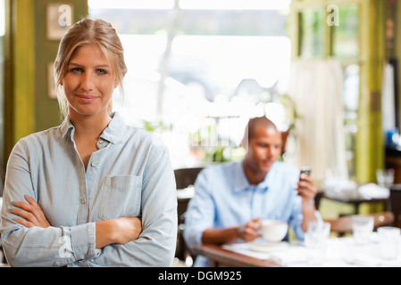 Una pareja en una cafetería de la ciudad. Una mujer sentada controlar un teléfono inteligente. Un hombre de pie con los brazos plegados.