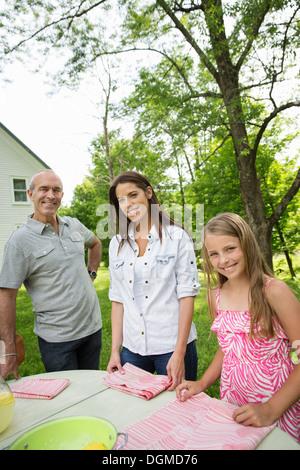 Una reunión familiar de verano en una granja. Tres personas de pie en una tabla, un padre y sus hijas. Dos niñas y un hombre maduro.