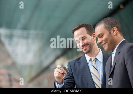 Ciudad. Dos hombres en trajes de negocios, mirando a un teléfono inteligente, sonriente.