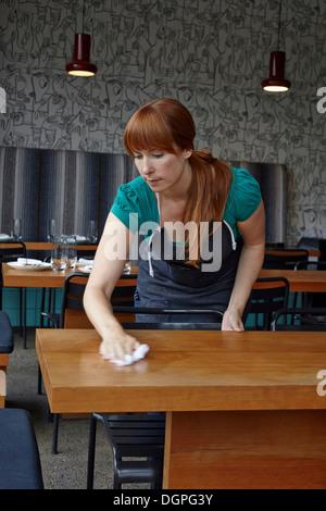 Mujer adulta media tabla de limpieza en restaurante.