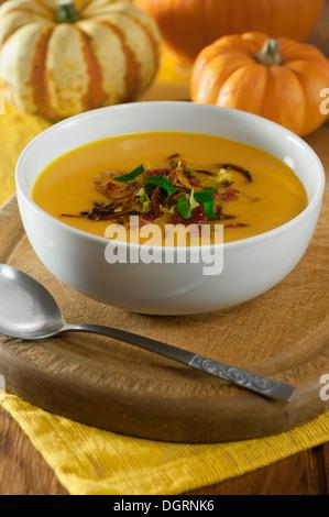 Sopa de calabaza con crujiente de tocino y cebollas.