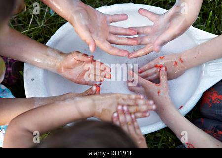 Niños lavándose las manos sucias, Munich, Baviera, Alemania