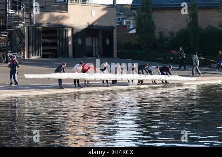 Los remeros levantando un bote fuera del agua en el río Cam Cambridge UK Foto de stock