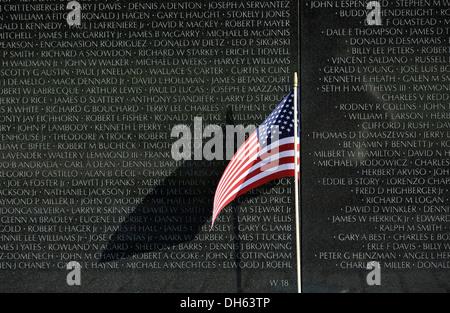 La bandera de los Estados Unidos volando en frente de la Vietnam Veterans Memorial Wall, memorial nacional con los nombres de los soldados estadounidenses caídos en