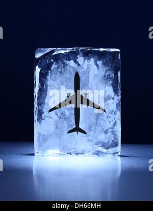 Un modelo de avión congelado en un bloque de hielo claro Foto de stock