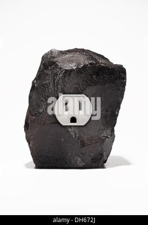 Un gran trozo de carbón negro con una sola toma de corriente eléctrica. Fondo blanco Foto de stock