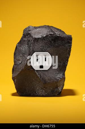 Un gran trozo de carbón negro con una sola toma de corriente eléctrica. Fondo de color amarillo brillante. Foto de stock