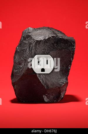 Un gran trozo de carbón negro con una sola toma de corriente eléctrica. Fondo rojo brillante Foto de stock