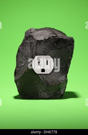 Un gran trozo de carbón negro con una sola toma de corriente eléctrica. Fondo verde brillante Foto de stock