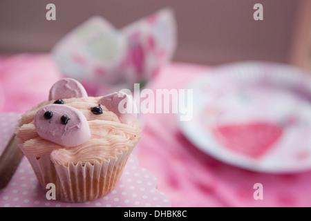 Una fiesta de cumpleaños mesa, con un paño, rosa y un cupcake decorado con la imagen de un cerdo.