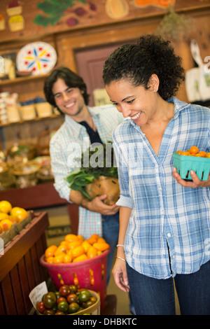 Dos personas con cestas de tomates y verduras de hoja rizada verde. Trabajando en una granja orgánica.